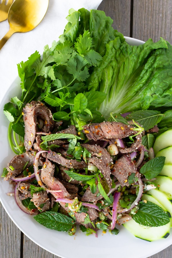 Overhead view of Beef Salad on a white plate garnished with lettuce, cucumbers, cilantro, and mint.