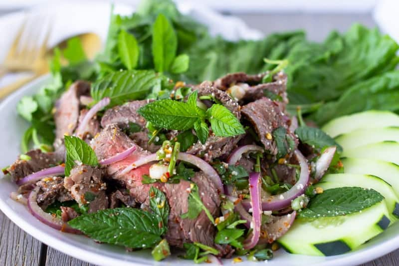 Wide angled shot of Thai Beef Salad on a white plate.