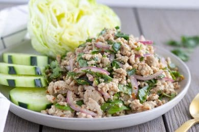 Horizontal view of finished Larb Gai on a plate with lettuce and cucumbers.