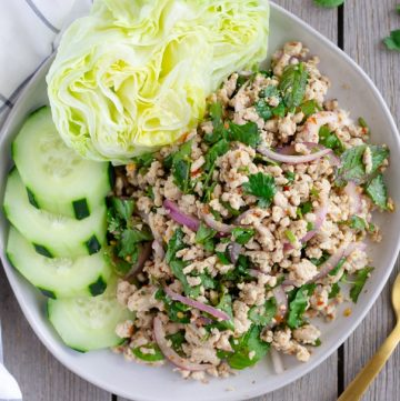 Overhead view of finished Larb Gai on a plate with lettuce and cucumbers.