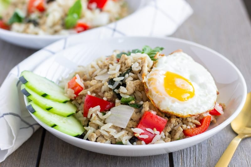 Two white bowls with finished Thai Basil Fried rice and topped with a fried egg.