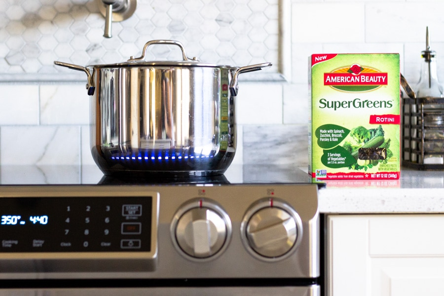 Pot on stove with box of Super Greens pasta next to it.