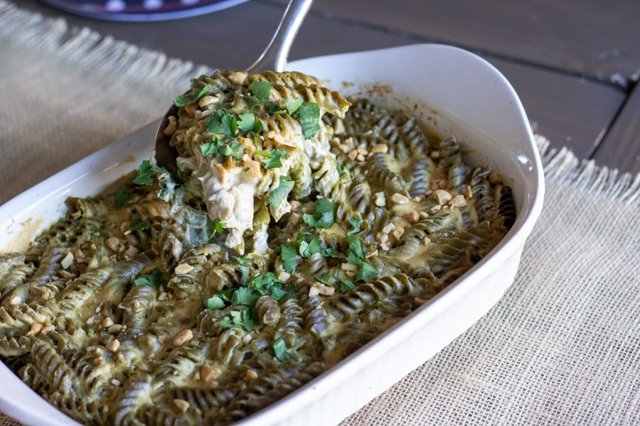 Finished salsa verde pasta bake in a white casserole dish with a spoon scooping up a portion.