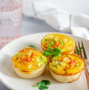 Three Sausage Egg quiche cups on a plate with a fork on the side and garnished with cilantro.