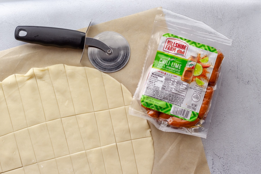 Pie crust on a sheet of parchment paper with a pizza cutter showing how to cut strips