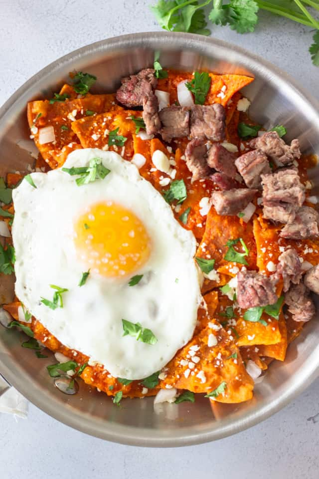 Chilaquiles Rojos topped with fried egg and pieces of carne asada on top.