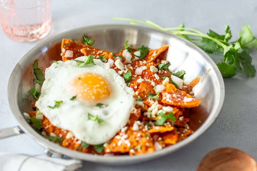 Chilaquiles in a skillet topped with a fried egg.