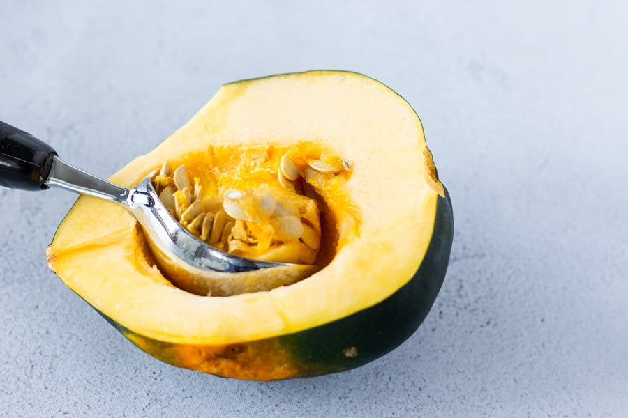 An ice cream scoop being used to scoop out the seeds inside the acorn squash.