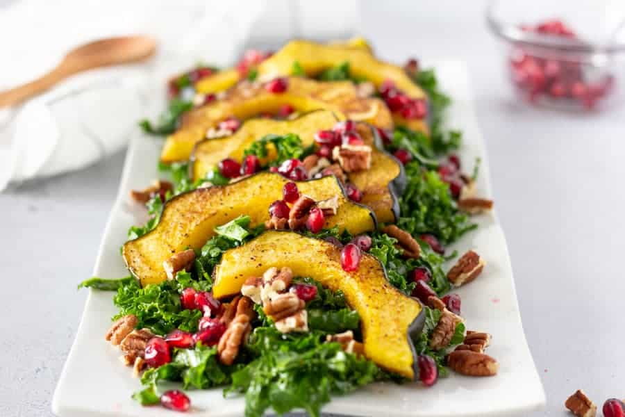 Complete kale salad with acorn squash and topped with pecans and pomegranates.