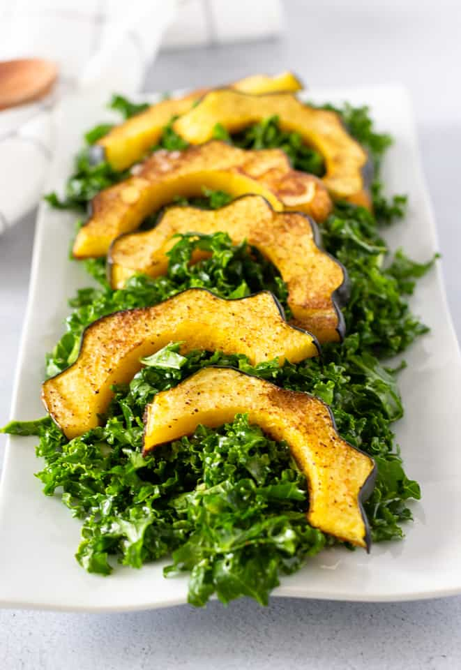 Kale Salad on a white plate topped with roasted acorn squash.