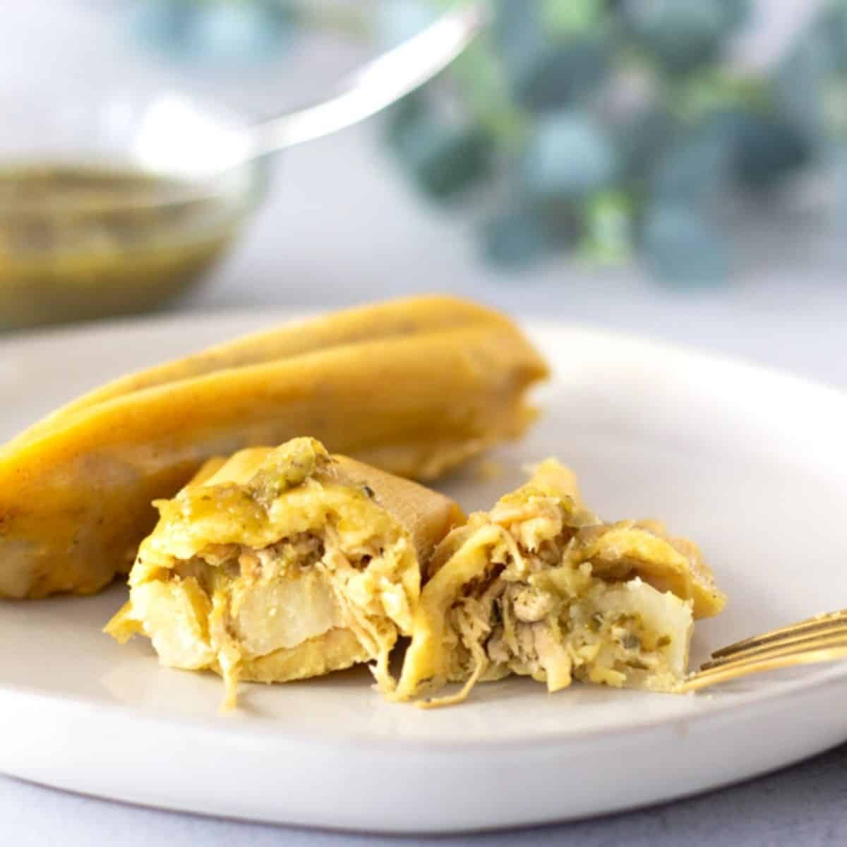 A Tamal on a plate that is cut in half to reveal the chicken filling