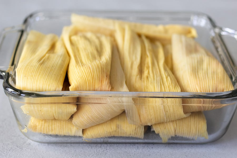 Wrapped tamales in a glass dish.