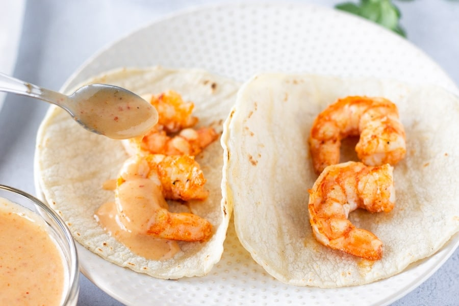 Two Pieces of shrimp on tortillas with red curry sauce being drizzled on top.
