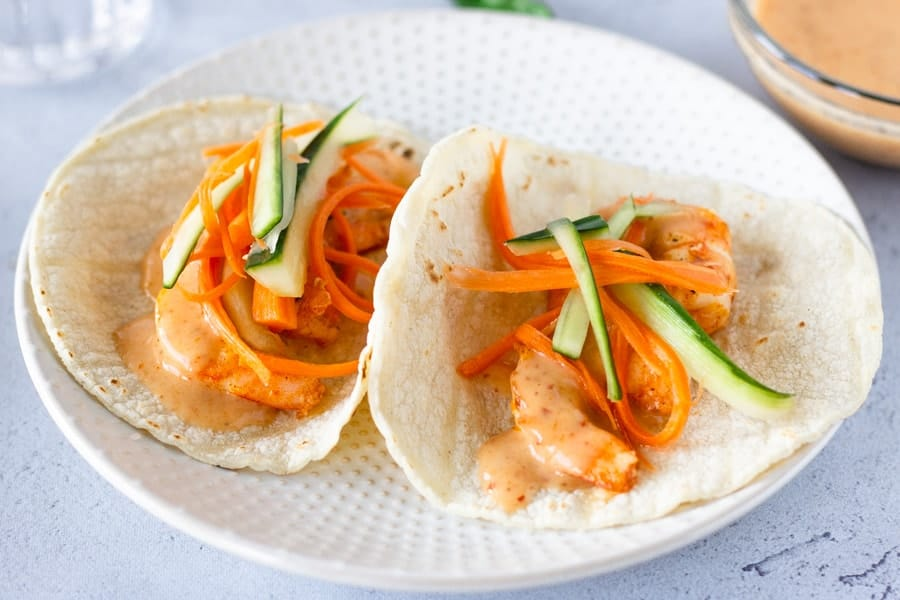 Two Tacos topped with pickled carrots and cucumbers.