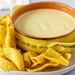 Queso in a bowl with corn chips on the side.