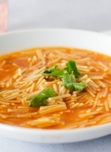 Fideo in a white bowl topped with cilantro leaves, and a gold spoon inside.