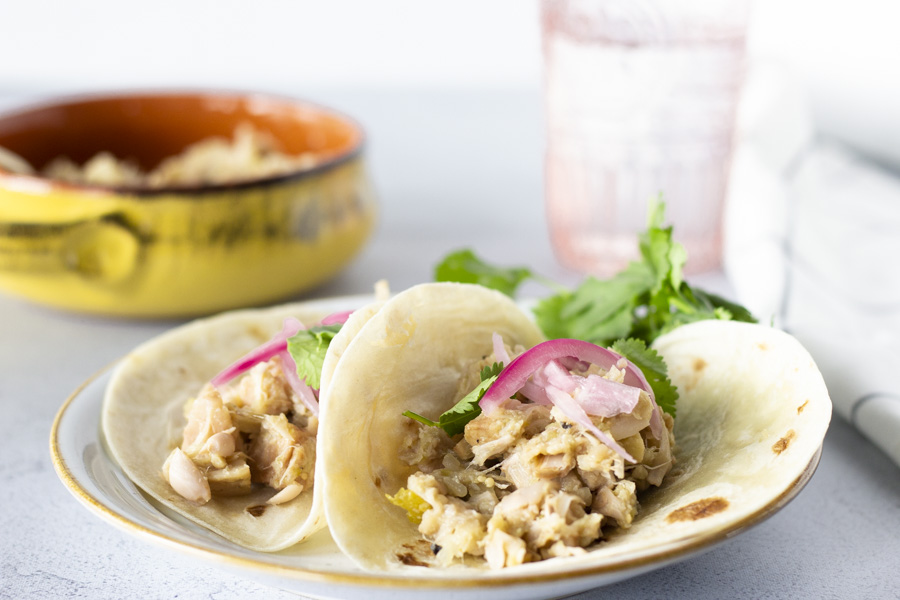 Horizontal view of two Jackfruit tacos topped with pickled onions on a plate with a bowl of salsa verde jackfruit on the side.