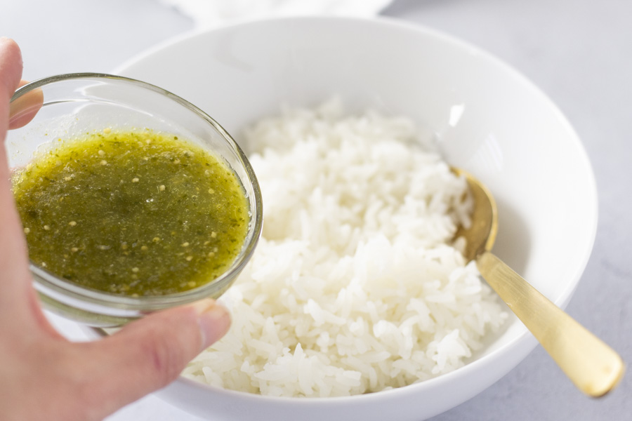 Hand holding a small dish of salsa verde over a bowl of white rice.