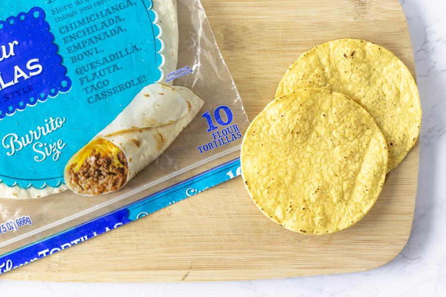 Burrito size flour tortilla and 2 crunchy tostadas on a cutting board.