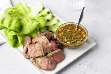Finished plate of Crying Tiger- sliced steak, lettuce leaves, sliced cucumbers, and dipping sauce.