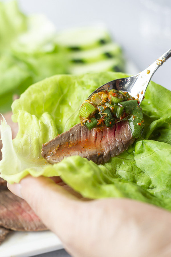 Hand holding a lettuce leaf with steak and dipping sauce being added with a spoon.