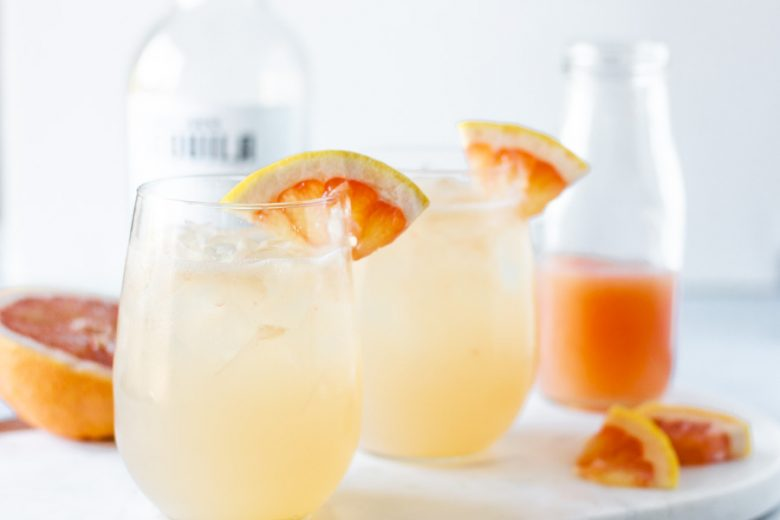 Landscape view of cocktail in stemless wine glasses and garnished with grapefruit slices.