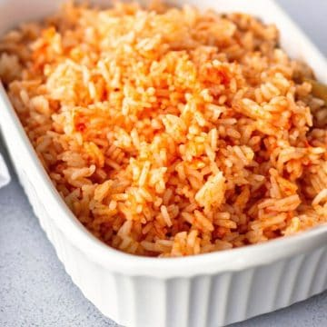 Red rice in a white serving dish.