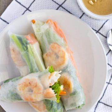 Overhead view of 3 rice paper rolls on a white plate.