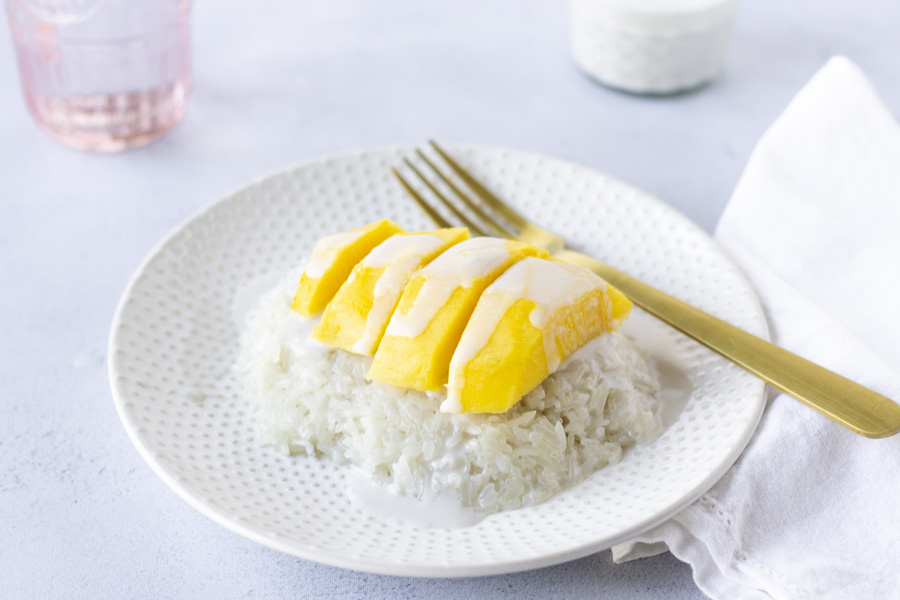 Sweet rice on a plate topped with mango and coconut milk, gold fork on the side.