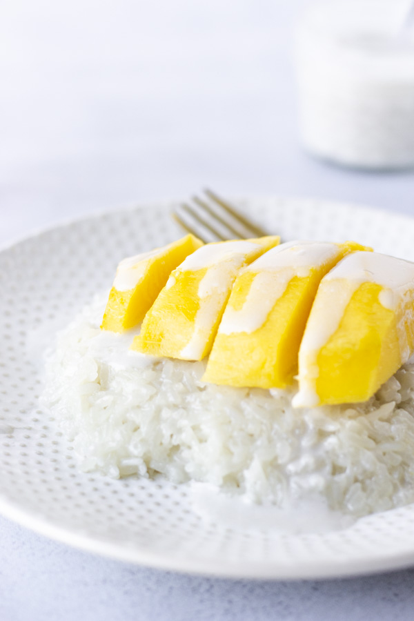 Sweet rice on a plate topped with mango and coconut milk.