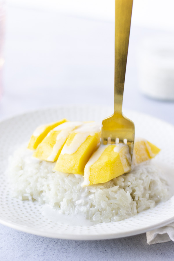 Gold fork piercing a mango on top of rice.