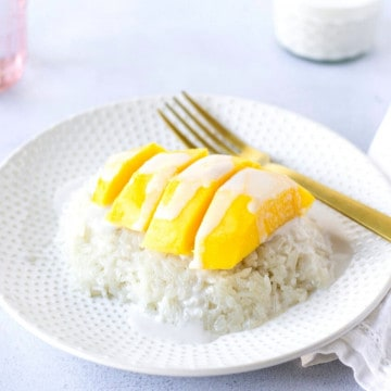 Plate with a mound of rice topped with sliced yellow mango and coconut sauce.