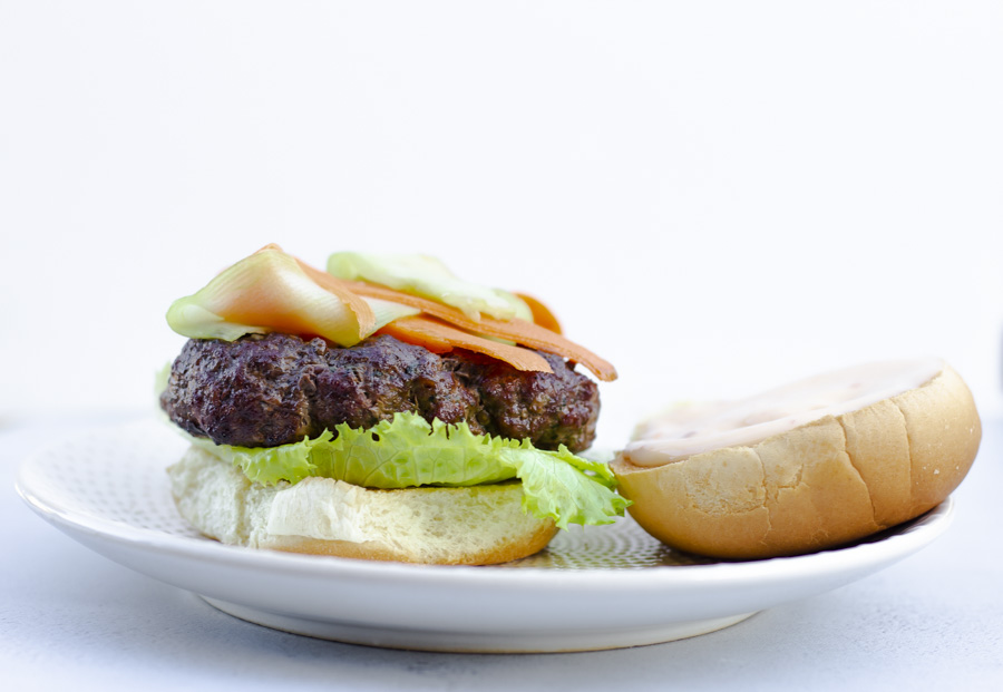 Horizontal view of burger with top bun on the side.