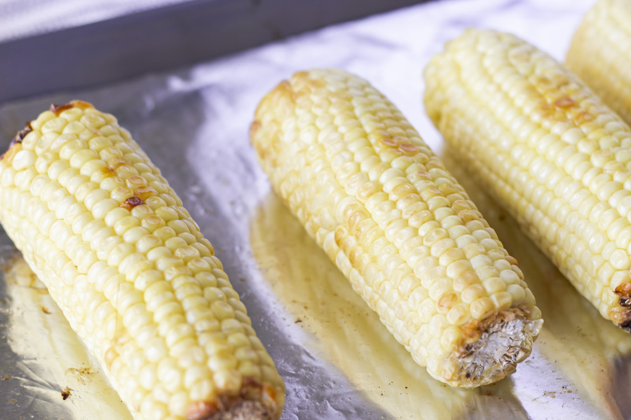Roasted ears of corn on a foil lined baking sheet.