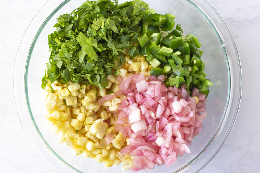 Ingredients for corn salsa in a bowl. Corn, red onion, jalapenos, and cilantro.