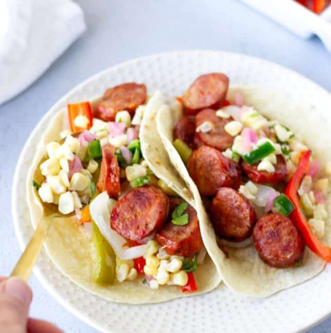 Hand holding a gold spoon of corn salsa over Cajun sausage tacos.