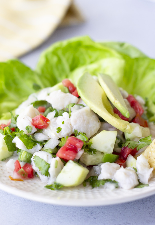 Fish ceviche on a plate with lettuce leaves and topped with avocado