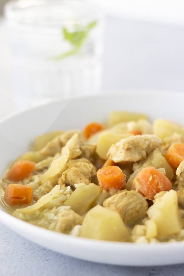 Curry in a white bowl with a clear glass of water in the back.