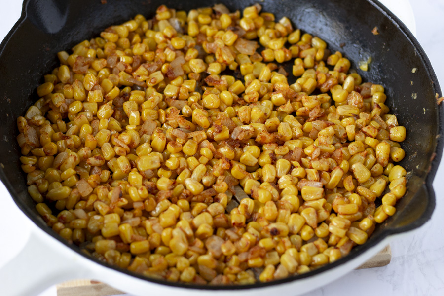 Corn cooking in a cast iron skillet.