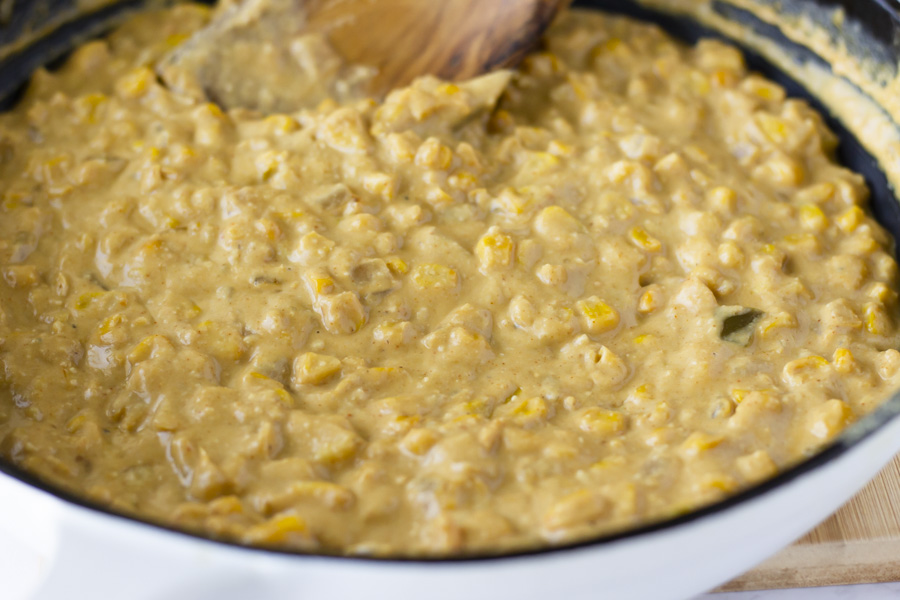 Cashew cream, corn, and onions cooking in a skillet.
