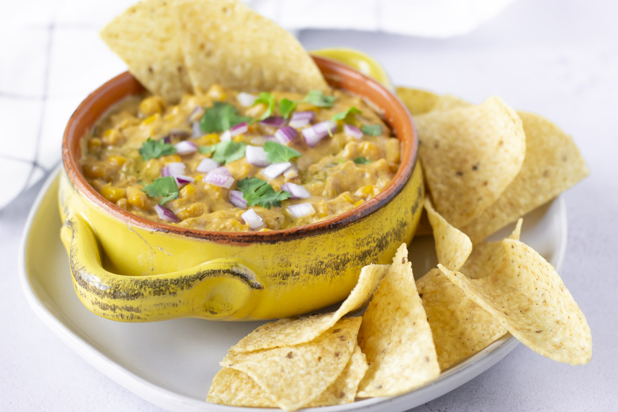 Horizontal view of dairy free elote dip in a yellow bowl with tortilla chips on the side.