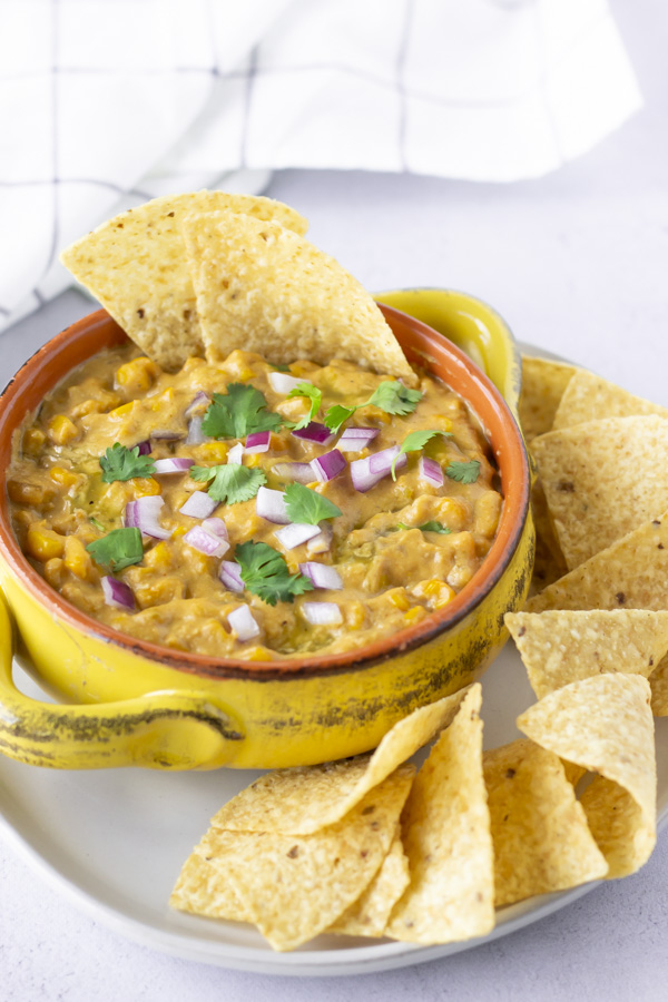 Mexican Street Corn Dip in a yellow bowl topped with red onions, cilantro, and tortilla chips.