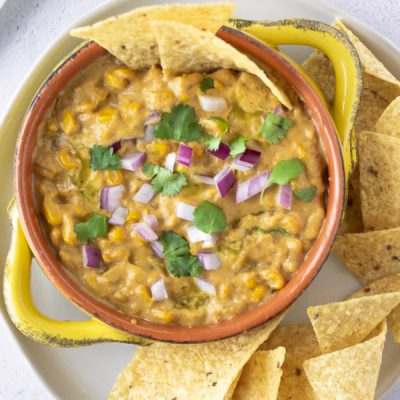 Overhead view of Elote Dip in a yellow bowl topped with red onions, cilantro, and tortilla chips.