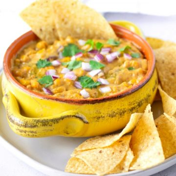 Yellow dish holding elote dip with chips on the side.