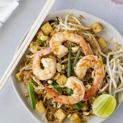 Overhead view of Pad Thai with chopsticks on the side and a glass of water.