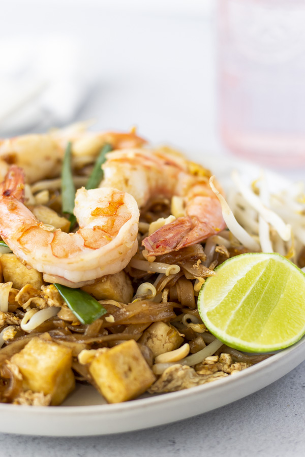 Up close view of shrimp on top of noodles and a lime wedge on the side.