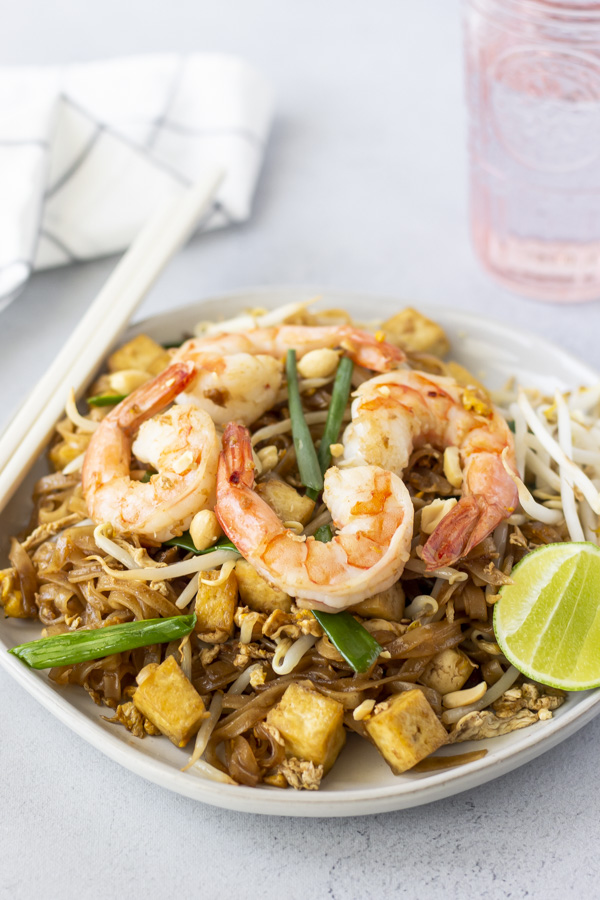 Pad Thai on a white plate with a lime wedge and chopsticks on the side.