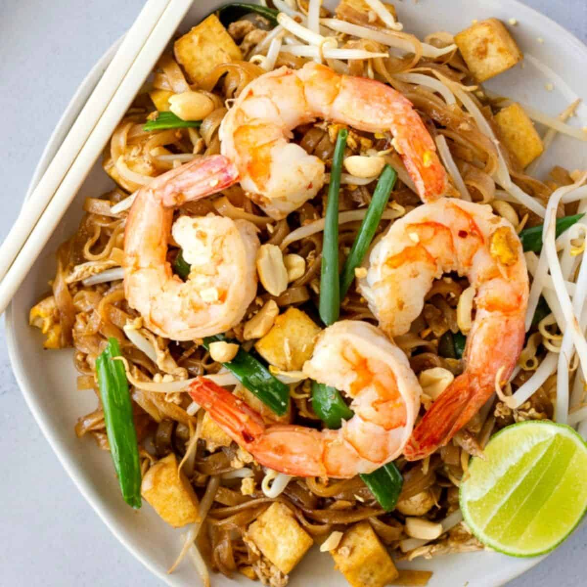 Overhead view of pad thai with shrimp on white plate with chopsticks on the side.