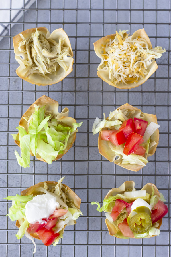 Overhead view of taco cups on a wire baking rack.