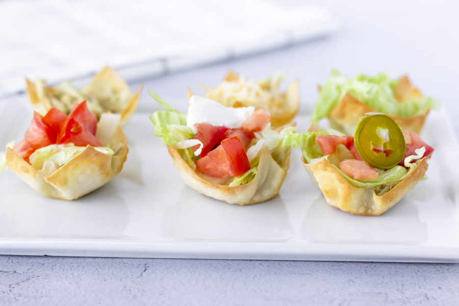 Horizontal view of six wonton cups on a white plate.